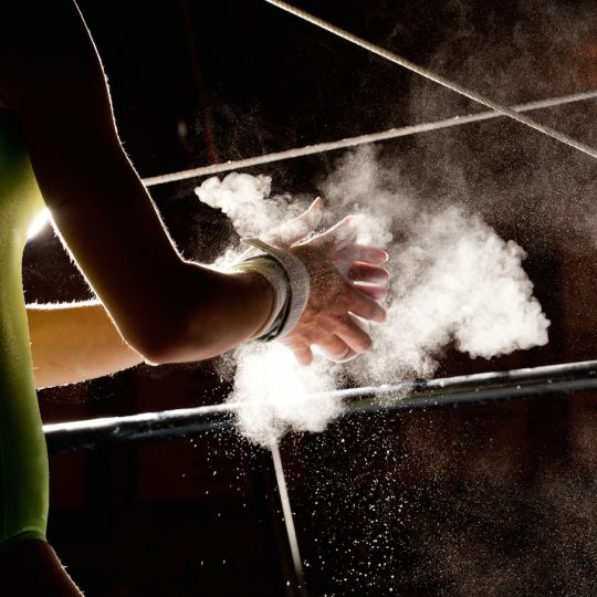 Stunning capture of an advanced women's gymnast prepping for her uneven bars routine. She has dipped her hands in the chalk and rubs off the excess.   Captured in with studio lighting giving high detail and feel of action to the tiny fragments of powder in mid air.