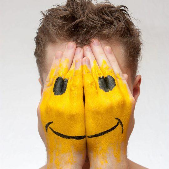 Portrait of a man hiding his face under smile mask