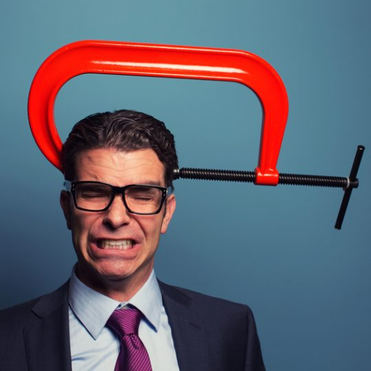 A businessman dressed in suit and wearing glasses is not responding well to business pressure. The c clamp on his head is causing him to grimace under lots of pressure.